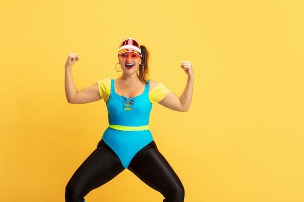 Junge kaukasische plus größe weibliches model training auf gelber wand. exemplar. konzept des sports, gesunder lebensstil, körperpositiv, mode, stil. stilvolle frau, die wie superheld aufwirft, mädchenpower.