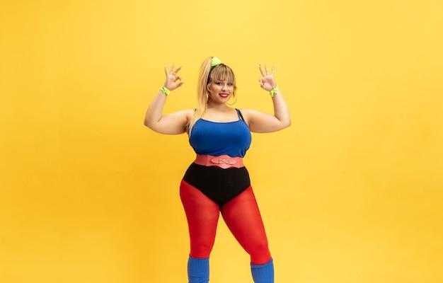 Junge kaukasische plus größe weibliches model training auf gelber wand. stilvolle frau in hellen kleidern. exemplar. konzept des sports, gesunder lebensstil, körperpositiv, mode. lächelnd, nett zeigend.