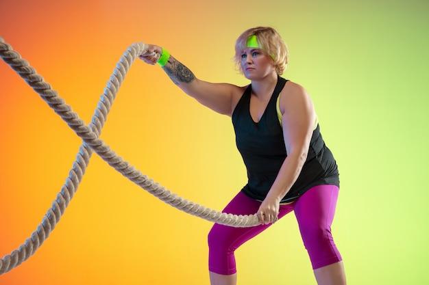 Junge kaukasische plus größe weibliches modelltraining auf gradientenorangenhintergrund im neonlicht. trainingsübungen mit den seilen machen. konzept von sport, gesundem lebensstil, körper positiv, gleichheit.