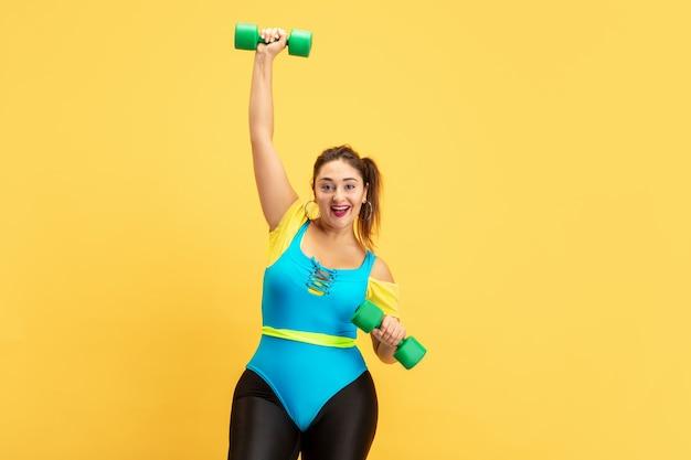 Junge kaukasische plus size weibliche model ausbildung auf gelb