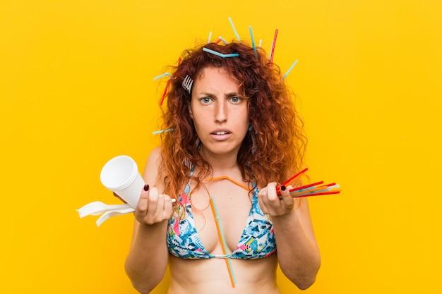 Junge kaukasische rothaarigefrau verärgert mit dem missbräuchlichen gebrauch des plastiks