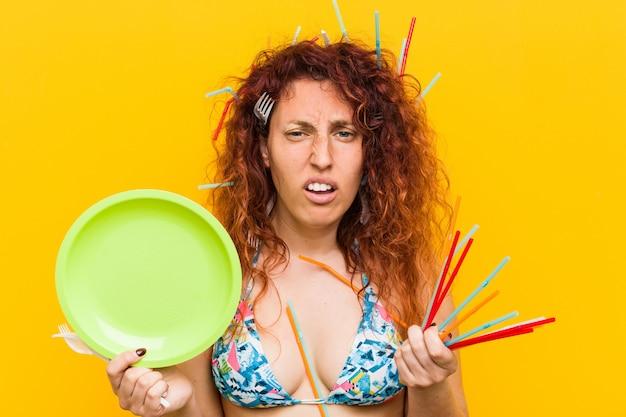 Junge kaukasische rothaarigefrau verärgert über den missbräuchlichen gebrauch des plastiks