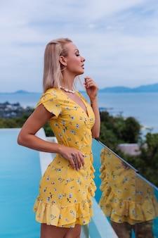 Junge kaukasische ruhige glückliche hübsche frau mit hellem abendmake-up, das gelbes sommerkleid und muschelhalskette trägt