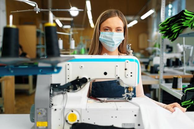 Junge kaukasische schneiderin, die in der nähfabrik arbeitet, die medizinische schutzmaske trägt.