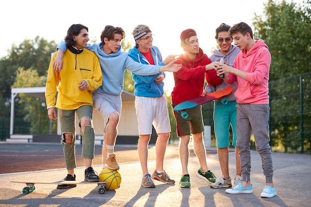 Junge kaukasische skateboarder trinken saft im freien