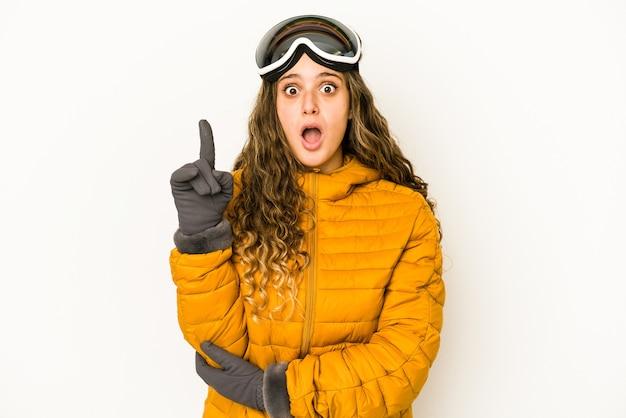 Junge kaukasische snowboarderfrau isoliert, die einige große idee, konzept der kreativität hat.