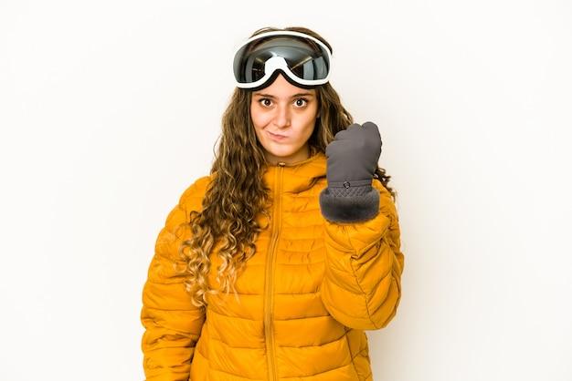 Junge kaukasische snowboarderfrau lokalisiert, die faust zur kamera, aggressiven gesichtsausdruck zeigt.
