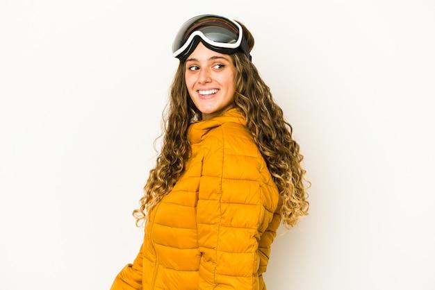 Junge kaukasische snowboarderin isoliert sieht beiseite lächelnd, fröhlich und angenehm aus.