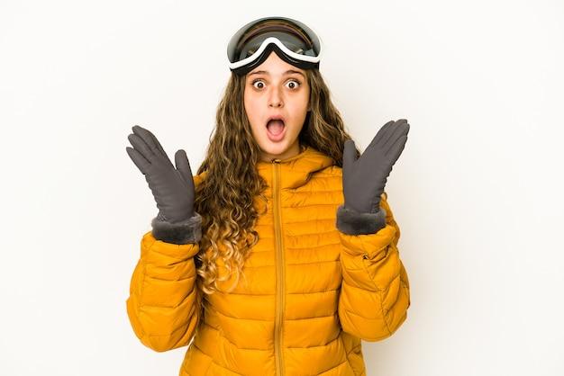 Junge kaukasische snowboarderin isoliert und überrascht.