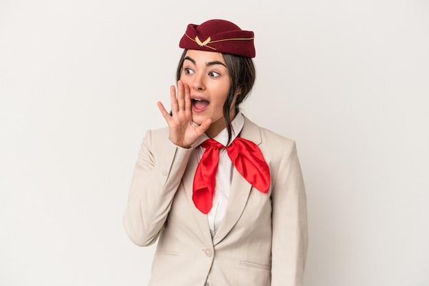 Junge kaukasische stewardessfrau lokalisiert auf weißem hintergrund, die palme nahe geöffnetem mund schreit und hält.