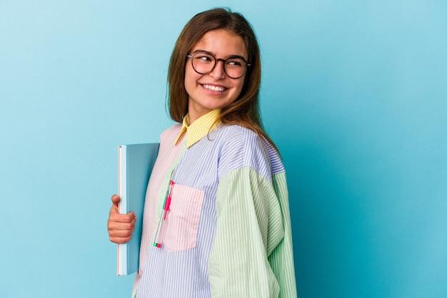 Junge kaukasische studentin, die bücher auf blauem hintergrund hält, sieht beiseite lächelnd, fröhlich und angenehm aus.