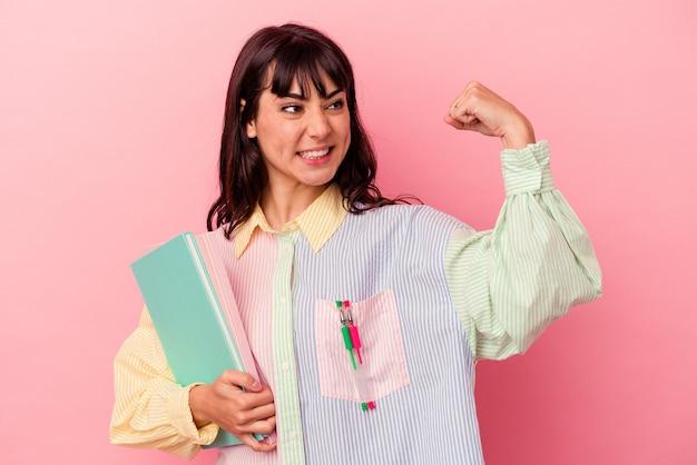 Junge kaukasische studentin, die bücher einzeln auf rosafarbenem hintergrund hält und die faust nach einem sieg anhebt, gewinnerkonzept.