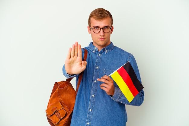 Junge kaukasische studentin, die deutsch studiert, isoliert auf weiß, stehend mit ausgestreckter hand, die stoppschild zeigt und sie verhindert.