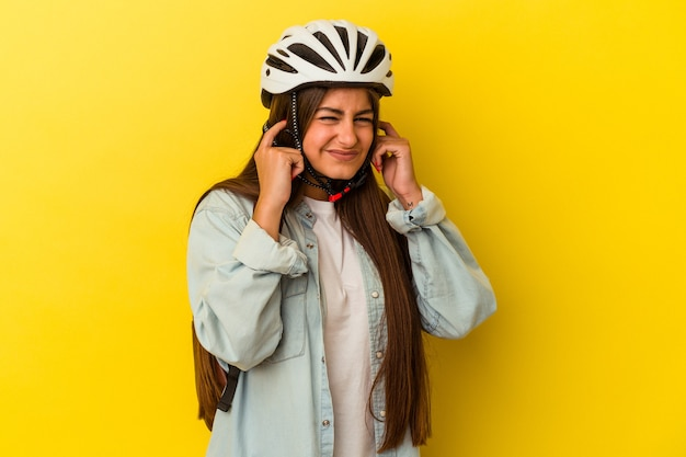 Junge kaukasische studentin, die einen fahrradhelm trägt, isoliert auf gelbem hintergrund, der die ohren mit den händen bedeckt.