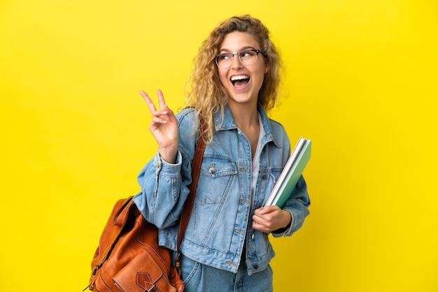 Junge kaukasische studentin isoliert auf gelbem hintergrund lächelt und zeigt victory-zeichen