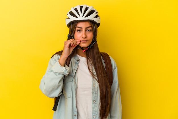 Junge kaukasische studentin trägt einen fahrradhelm auf gelbem hintergrund mit fingern auf den lippen, die ein geheimnis halten.