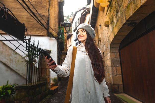 Junge kaukasische touristenfrau, die das smartphone in einer alten stadt verwendet.