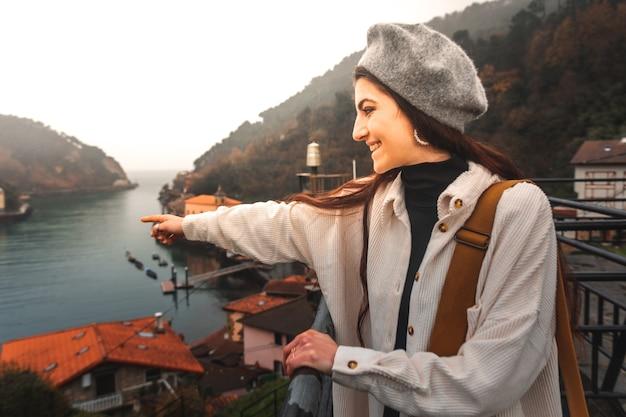 Junge kaukasische touristenfrau, die die bucht von einem hohen standpunkt bei pasaia betrachtet; baskenland.