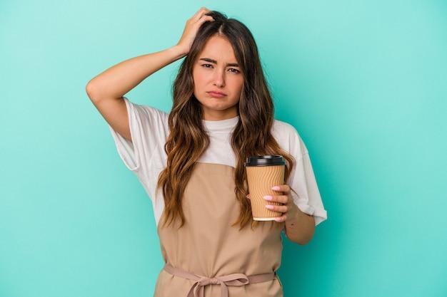 Junge kaukasische verkäuferin, die einen kaffee zum mitnehmen auf blauem hintergrund hält und schockiert ist, hat sich an ein wichtiges treffen erinnert.