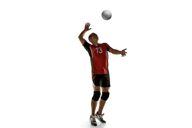 Junge kaukasische volleyballspielerin, die isoliert auf weißer wand praktiziert männliches sportlertraining mit dem ball in bewegung und aktion. sport, gesunder lebensstil, aktivität, bewegungskonzept. exemplar.