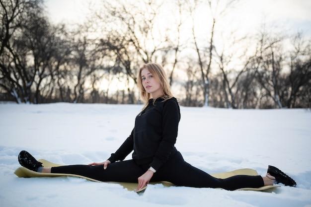 Junge kaukasische weibliche blondine in den gamaschen, welche die übung sitzt auf einer schnur am freilicht im schneebedeckten wald ausdehnen. fit und sportlicher lebensstil