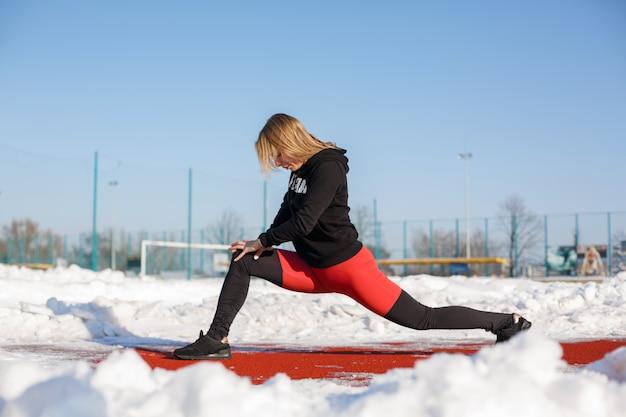 Junge kaukasische weibliche blondine in den violetten gamaschen, die übung auf einer roten laufbahn in einem schneebedeckten stadion ausdehnen. fit und sportlicher lebensstil
