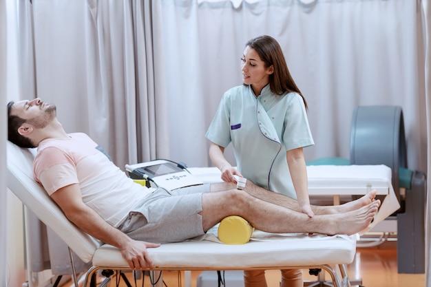 Junge kaukasische weibliche krankenschwester, die elektrolysegerät verwendet, um patienten knieverletzung zu heilen.