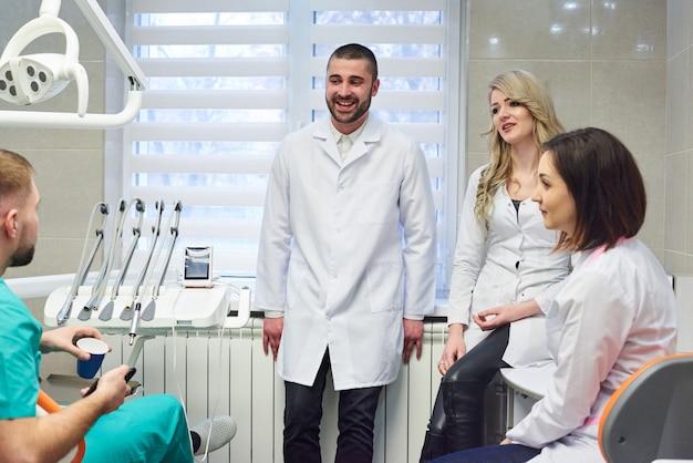 Junge kaukasische zahnarztgruppe auf kaffeepause