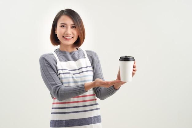 Junge kellnerin des cafés in der schürze, die ihnen ein glas heißen kaffee gibt, während sie isoliert vor der kamera steht