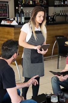 Junge kellnerin, die bestellung auf digitaler tablette in der bar entgegennimmt