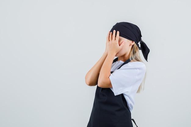 Junge kellnerin, die hände auf gesicht in uniform und schürze hält