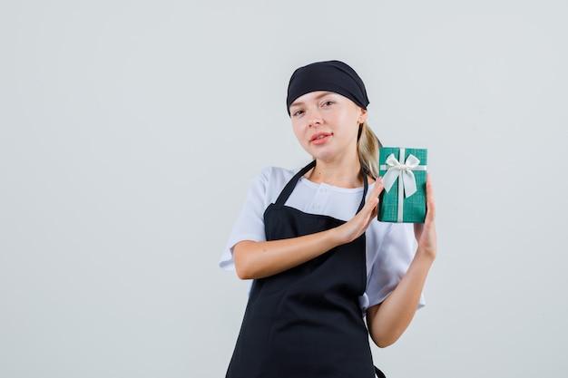 Junge kellnerin hält geschenkbox in uniform und schürze und sieht positiv aus