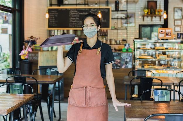Junge kellnerin in der medizinischen maske, die tablett hält, das im café steht.