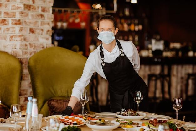 Junge kellnerin in uniform mit medizinischer maske und handschuhen, die im restaurant dienen. speicherplatz kopieren.