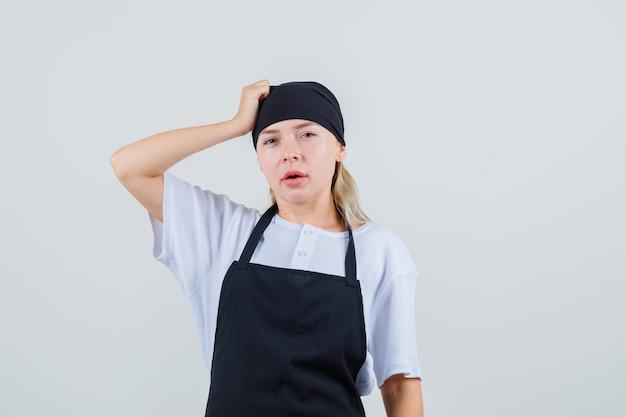 Junge kellnerin in uniform und schürze, die hand auf kopf hält und nachdenklich aussieht