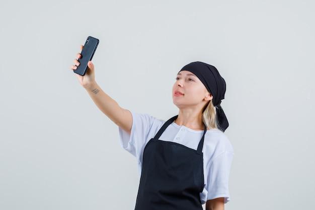 Junge kellnerin in uniform und schürze, die selfie auf handy nimmt