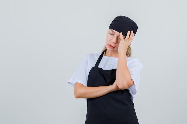 Junge kellnerin stützt kopf auf erhobene hand in uniform und schürze und sieht müde aus