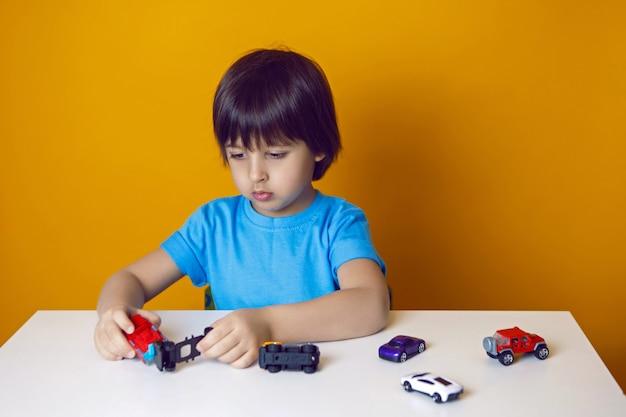 Junge kind in einem blauen t-shirt sitzt an einem tisch und spielt mit einem spielzeugauto