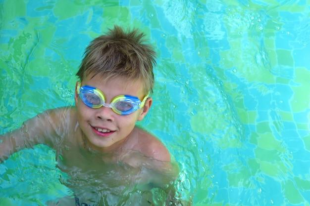 Junge kind in wassergläsern im pool. kinder schwimmen in einem privaten pool. sportferien.