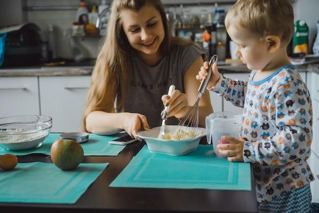 Junge kind mit mama in der küche kuchen kochen