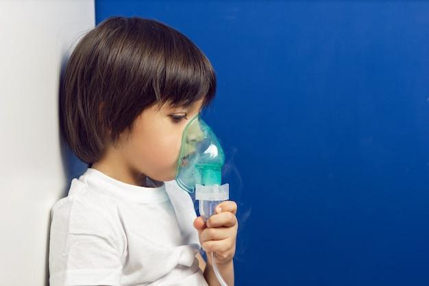 Junge kind unterzieht sich behandlung atmet inhalation grüne maske an der wand einer blauen wand in einer kinderklinik
