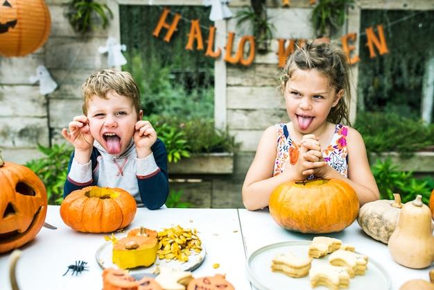 Junge kinder, die halloween-kürbislaternen schnitzen