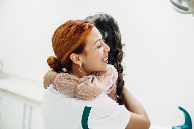 Junge kinderzahnärztin, die lächelt, während sie ihren kleinen mädchenpatienten vor der zahnuntersuchung umarmt.