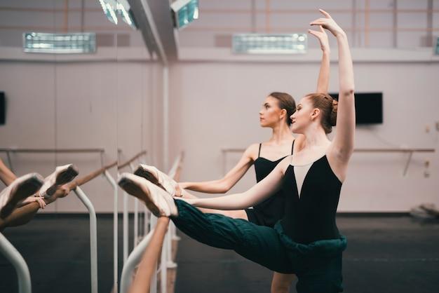Junge klassische weibliche tänzer, die im tanzstudio üben
