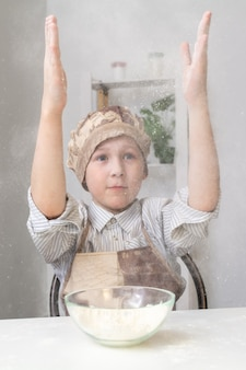 Junge klatscht in die hände mit mehl, eine mehlwolke steigt auf