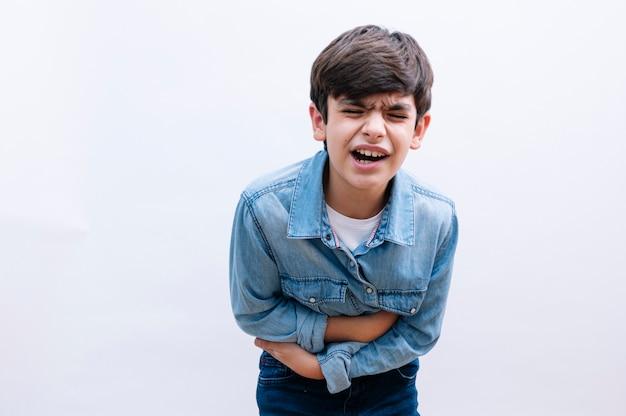 Junge kleine junge, die elegantes hemd trägt, das über mit lokalisiertem hintergrund mit hand auf magen steht, weil übelkeit, schmerzhafte krankheit sich unwohl fühlen. schmerzkonzept.
