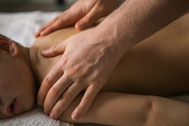 Junge kleinkind entspannt sich von einer therapeutischen massage. physiotherapeut arbeitet mit patienten in der klinik auf dem rücken eines kindes