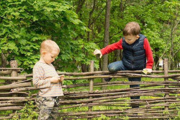 Junge klettert über einen rustikalen holzzaun im ländlichen wald rural