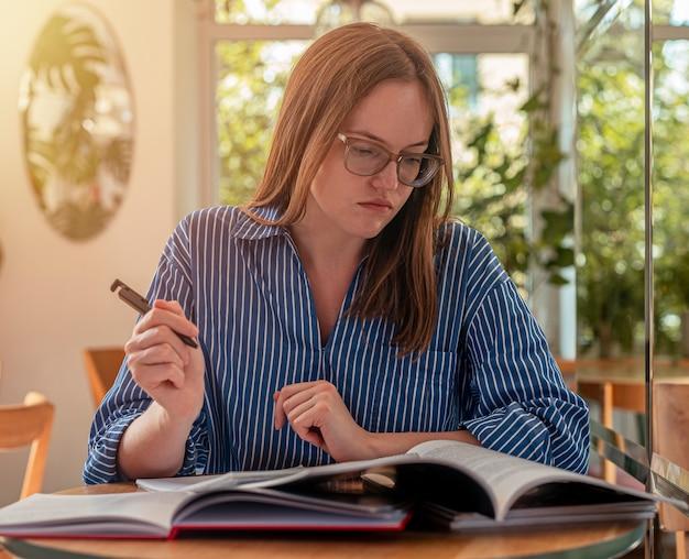 Junge kluge frau, die pläne im tagebuch schreibt und notizen macht, die mit akademischen büchern planen und recherchieren.