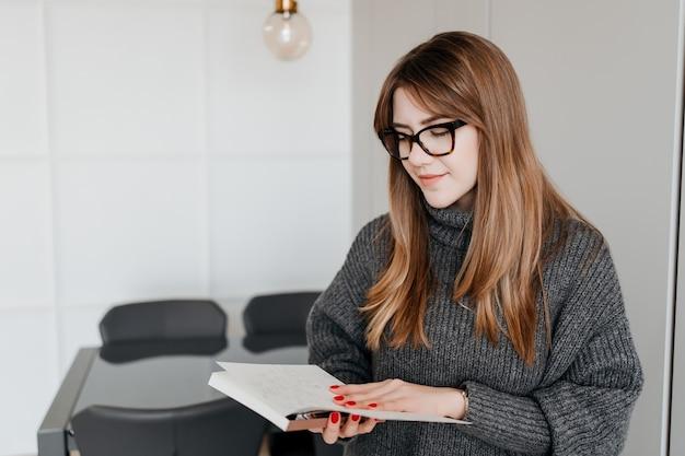 Junge kluge frau mit brille, die ein notizbuch liest und zu hause lächelt